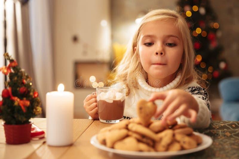 Bambina divertente con la tazza di cioccolata calda che prende biscotto da immagini stock libere da diritti