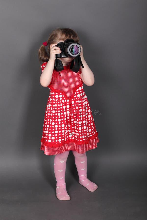 Bambina divertente nei tiri rossi del vestito fotografie stock libere da diritti