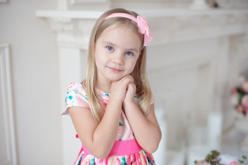 Bambina dolce che tiene le sue mani sotto il suo mento immagine stock libera da diritti