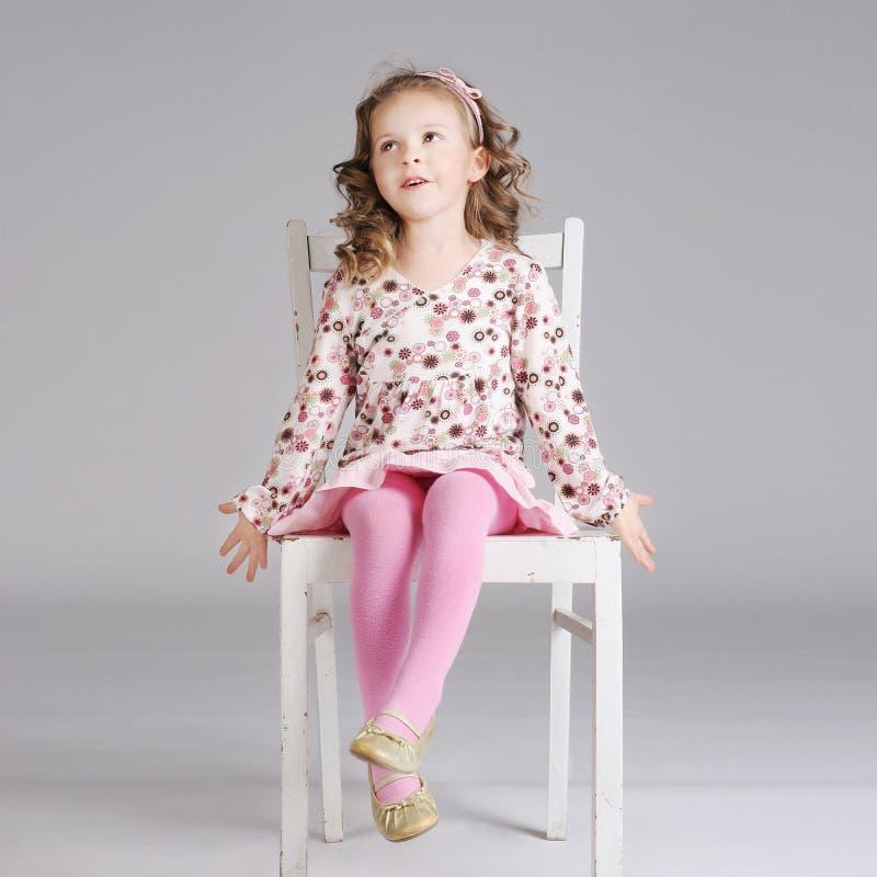 Foto della bambina dolce alla moda che posa sulla sedia bianca immagini stock libere da diritti