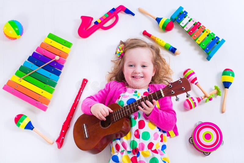 Bambina dolce con gli strumenti di musica immagine stock