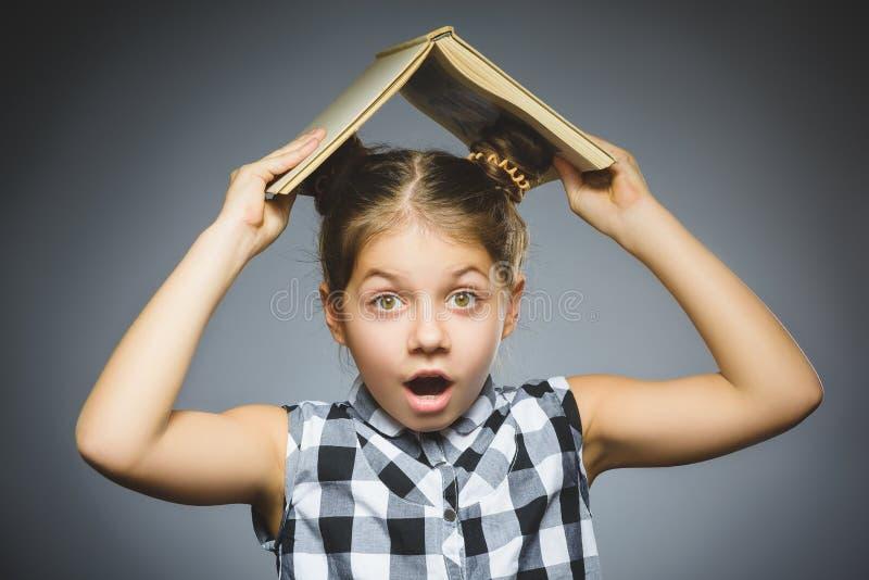 Bambina domandantesi con sorridere del libro isolato su fondo grigio fotografia stock libera da diritti