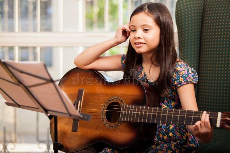 Bambina durante la lezione della chitarra fotografia stock
