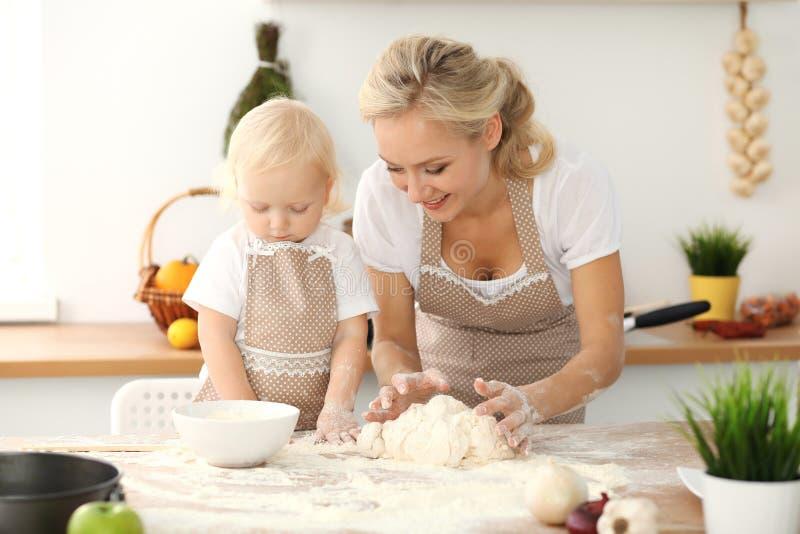 Bambina e la sua mamma bionda in grembiuli beige che giocano e che ridono mentre impastando la pasta in cucina Pasticceria casali fotografie stock