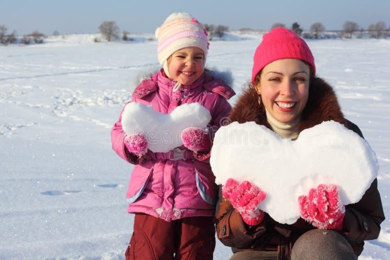Bambina e madre con i cuori nevosi immagini stock libere da diritti