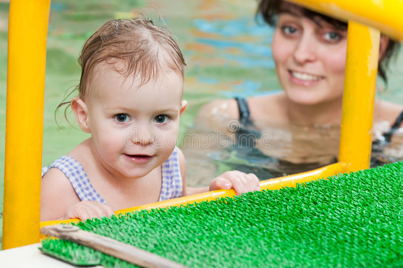 Bambina e mothe nel nuoto immagini stock