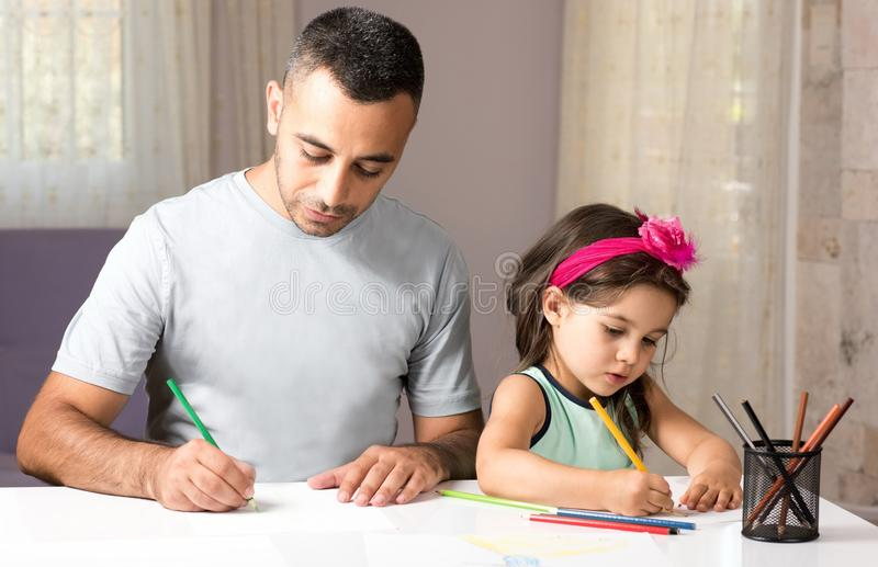 Bambina e padre Drawing Pictures Together immagine stock