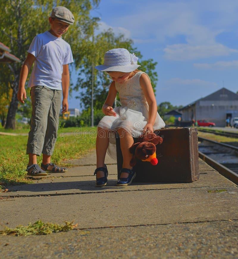 Bambina e ragazzo adorabili su una stazione ferroviaria, aspettante il treno con la valigia d'annata Viaggio, festa e fotografia stock libera da diritti