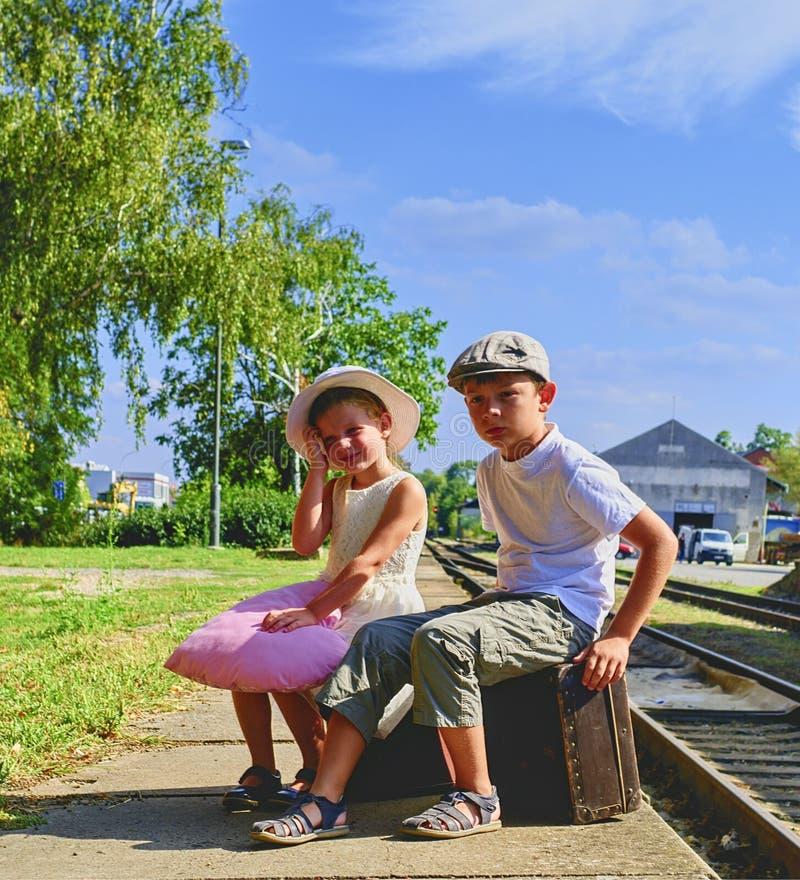 Bambina e ragazzo adorabili su una stazione ferroviaria, aspettante il treno con le valigie d'annata Viaggio, festa e chilhood c fotografia stock