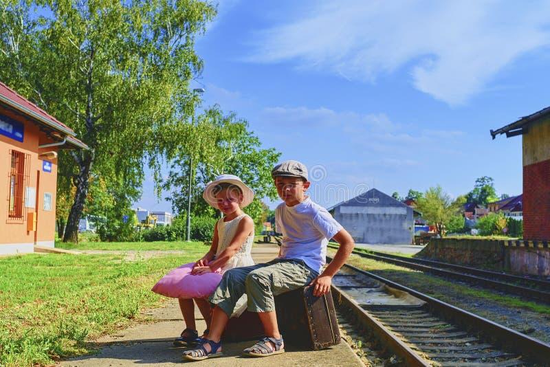Bambina e ragazzo adorabili su una stazione ferroviaria, aspettante il treno con le valigie d'annata Viaggio, festa e chilhood c fotografie stock