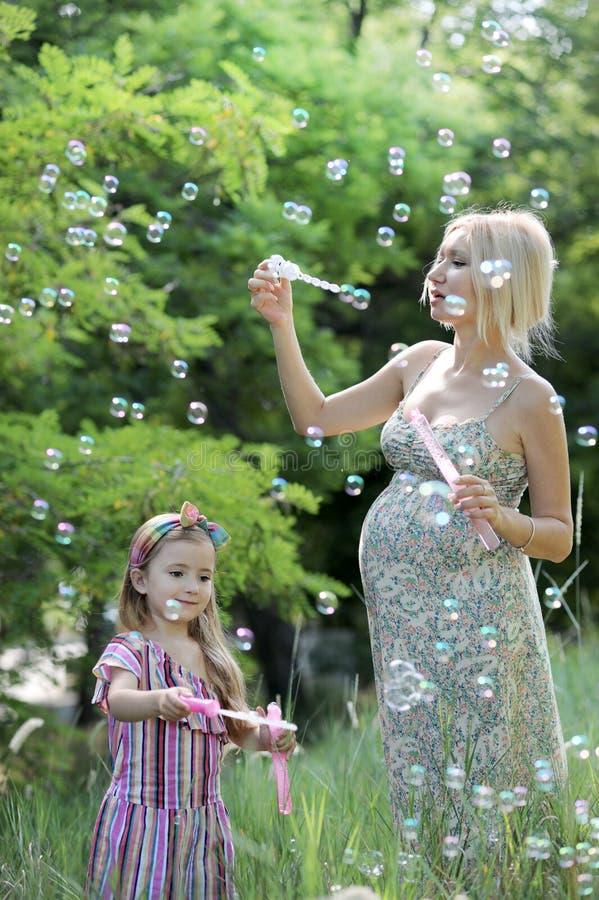 Bambina e sua madre incinta che giocano le bolle di sapone di salto immagine stock