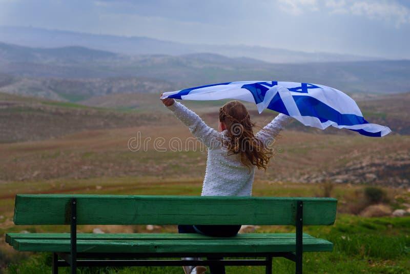 Bambina ebrea israeliana con la vista posteriore della bandiera di Israele fotografie stock