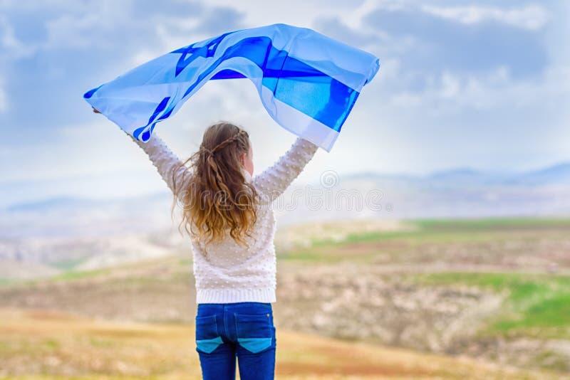 Bambina ebrea israeliana con la vista posteriore della bandiera di Israele fotografia stock libera da diritti