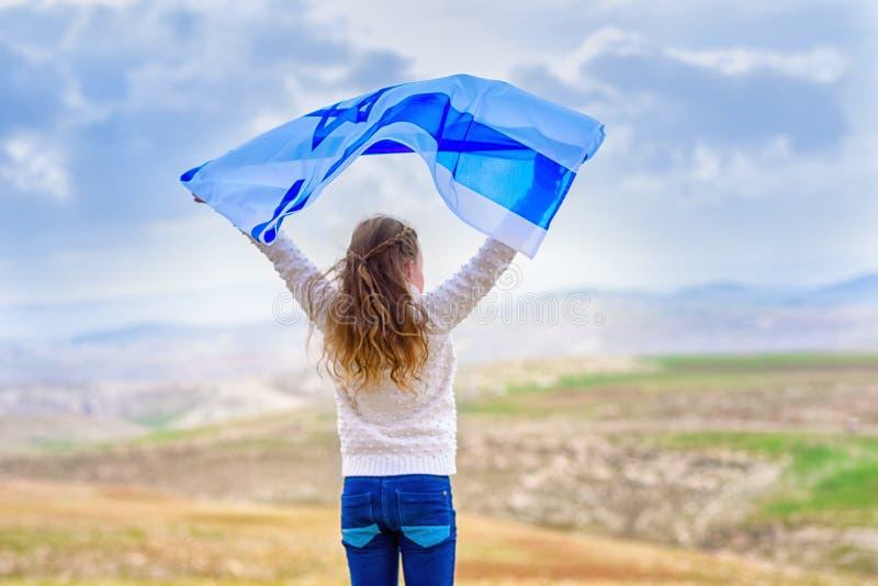 Bambina ebrea israeliana con la vista posteriore della bandiera di Israele immagini stock