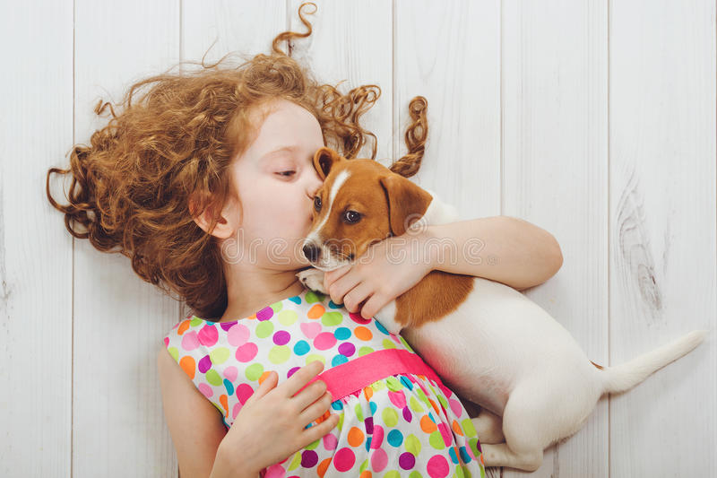Bambina ed i suoi bisbigli del cucciolo su fondo di legno immagini stock