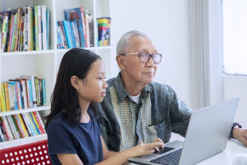 Bambina ed suo nonno che utilizza computer portatile nella biblioteca immagine stock