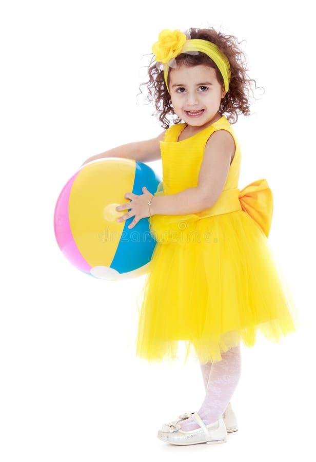 Bambina elegante e mora in un vestito giallo fotografia stock