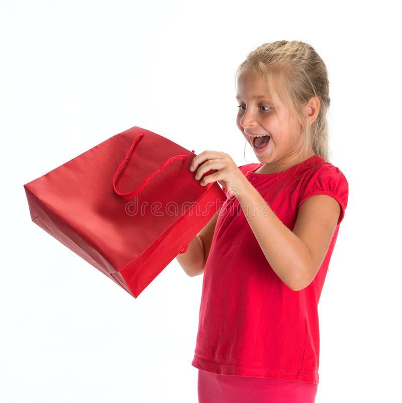 Bambina emozionante che sembra sacchetto della spesa interno immagine stock
