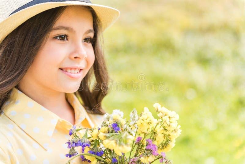 Bambina emozionante con i wildflowers sul campo immagine stock