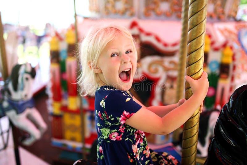 Bambina emozionante felice che guida il carosello ad un carnevale immagine stock