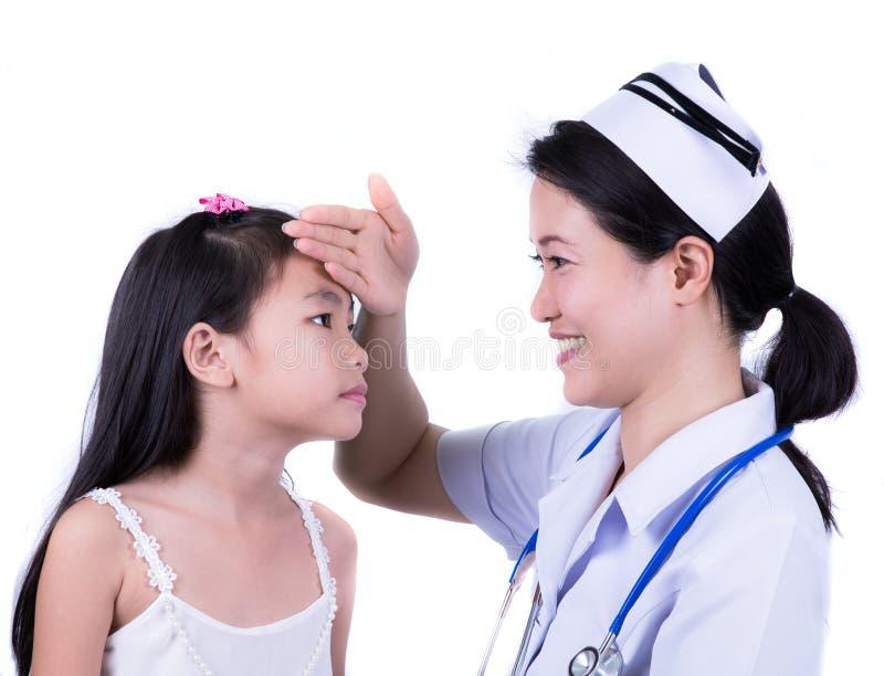 Bambina felice all'infermiere per un controllo - essendo esaminando fotografia stock