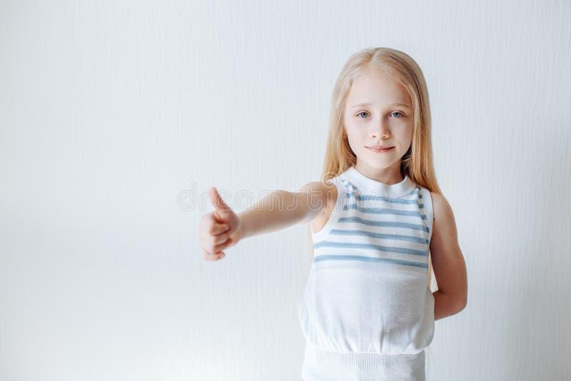 Bambina felice Bambina allegra che mostra i suoi pollici su mentre stando sul fondo bianco Copi lo spazio fotografie stock libere da diritti