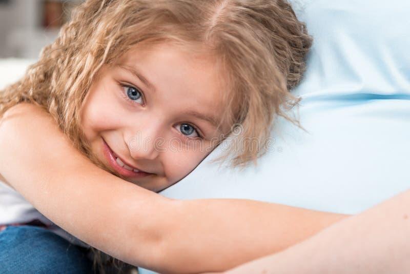 Bambina felice che abbraccia madre incinta immagini stock libere da diritti