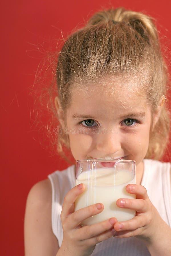 Bambina felice che beve mil fotografia stock libera da diritti