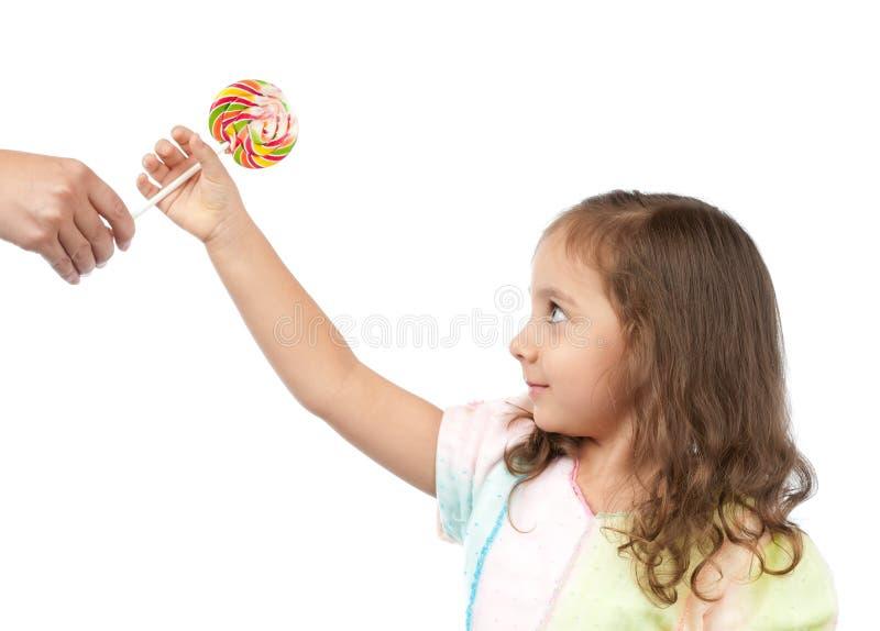 Bambina felice che cattura caramella dalla sua madre fotografia stock libera da diritti
