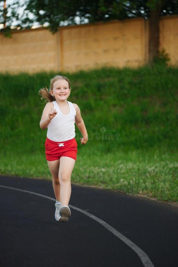 Bambina felice che corre sullo stadio immagine stock libera da diritti