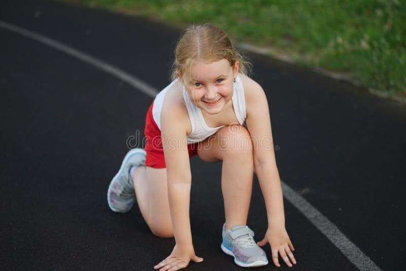 Bambina felice che corre sullo stadio fotografia stock