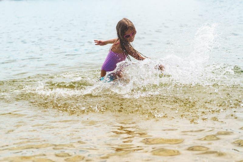 Bambina felice che gioca nelle onde di acqua bassa Bambina felice fotografia stock