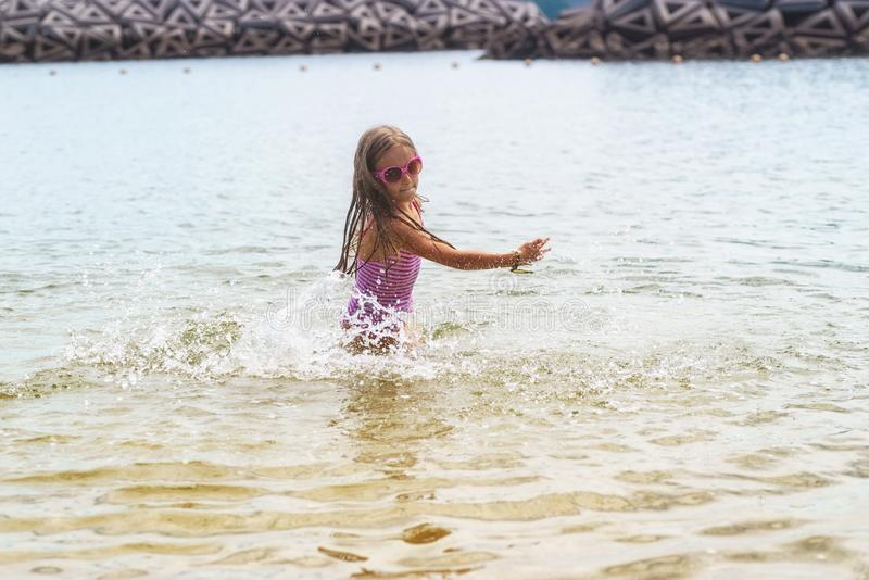 Bambina felice che gioca nelle onde di acqua bassa La ragazza sta giocando con le onde Bambina che gioca nelle onde in mare sulla immagini stock libere da diritti