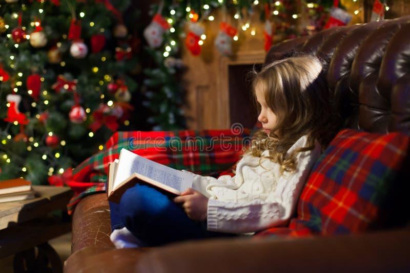 Bambina felice che legge un libro di storia vicino sullo strato in un accogliente fotografia stock