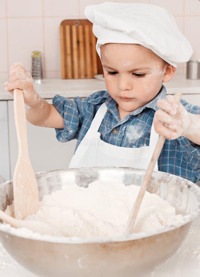 Bambina felice che produce la pasta della pizza immagine stock libera da diritti