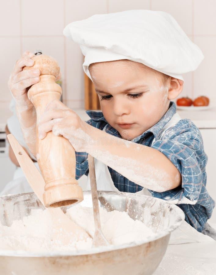 Bambina felice che produce la pasta della pizza immagini stock libere da diritti