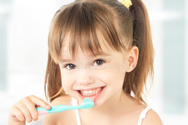 Bambina felice che pulisce i suoi denti fotografia stock libera da diritti