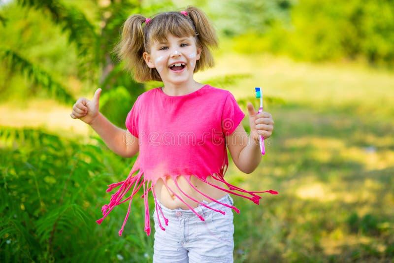 Bambina felice che pulisce i suoi denti con i pollici su L'igiene dentale fotografia stock