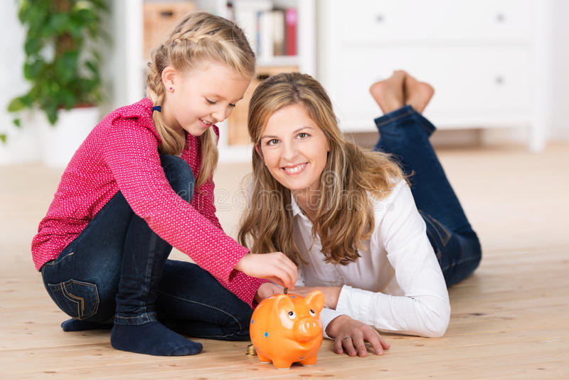 Bambina felice che risparmia il suo denaro per piccole spese fotografie stock