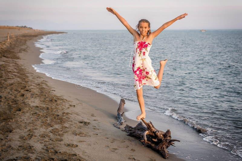 Bambina felice che sta sull'albero sulla spiaggia fotografie stock libere da diritti