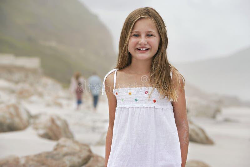 Bambina felice che sta sulla spiaggia fotografia stock