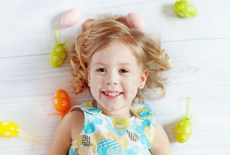 Bambina felice che tiene le uova di Pasqua fotografia stock
