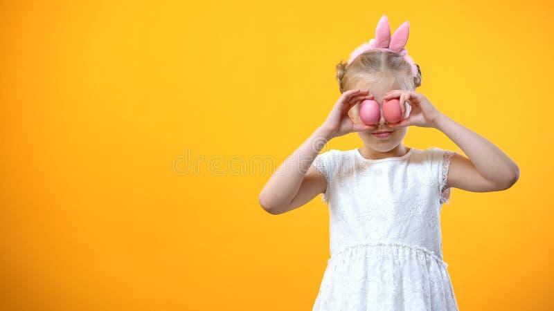 Bambina felice che tiene le uova di Pasqua colorate in occhi anteriori, sorridenti sulla macchina fotografica fotografie stock libere da diritti