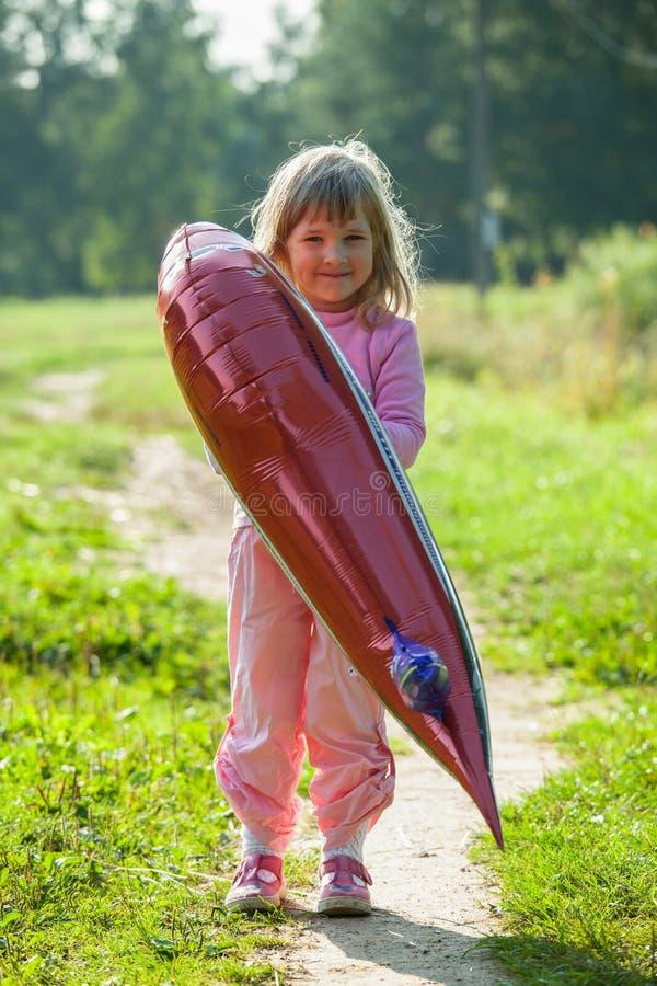 Bambina felice che tiene un grande pallone fotografia stock libera da diritti