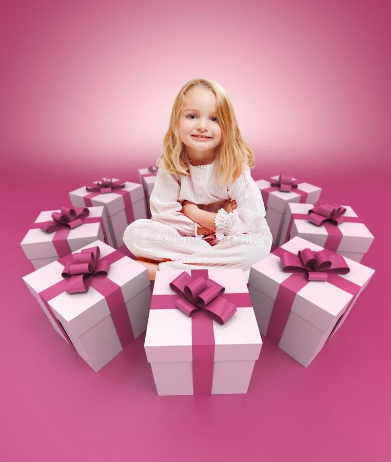 Bambina felice circondata dal rosa dei regali fotografia stock