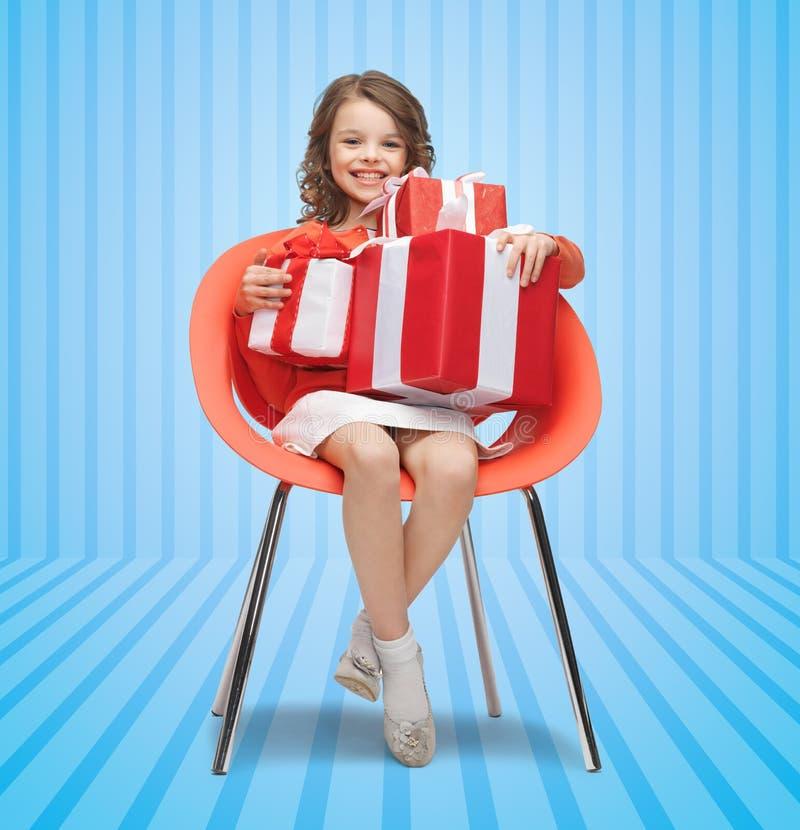 Bambina felice con i contenitori di regalo che si siedono sulla sedia fotografia stock libera da diritti
