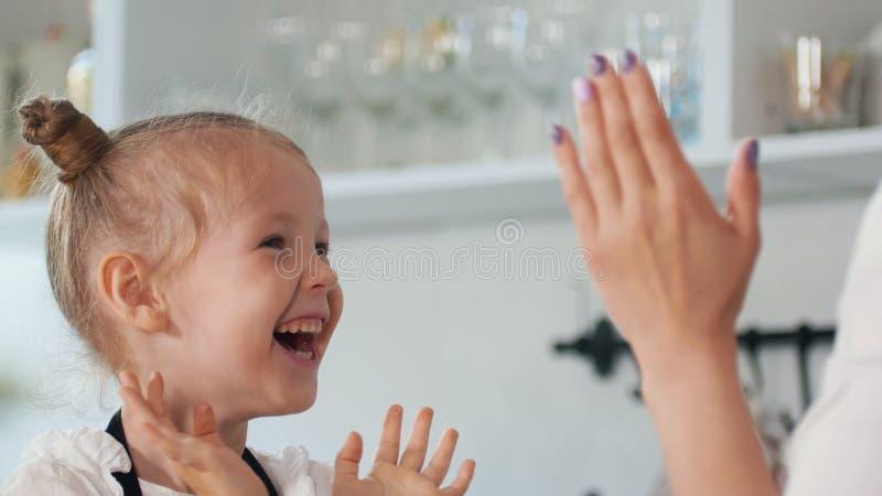 Bambina felice con il suo applauso della madre le loro mani nella cucina fotografia stock