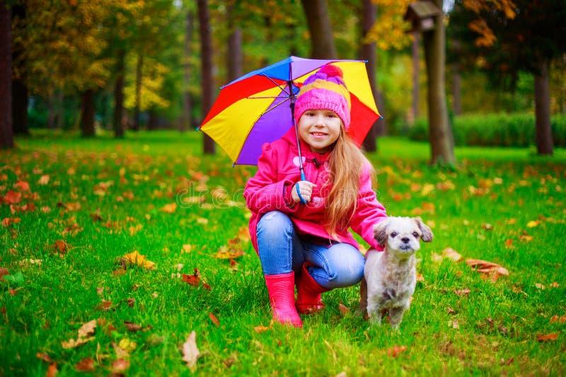 Bambina felice con il suo cane nel parco di autunno fotografia stock libera da diritti