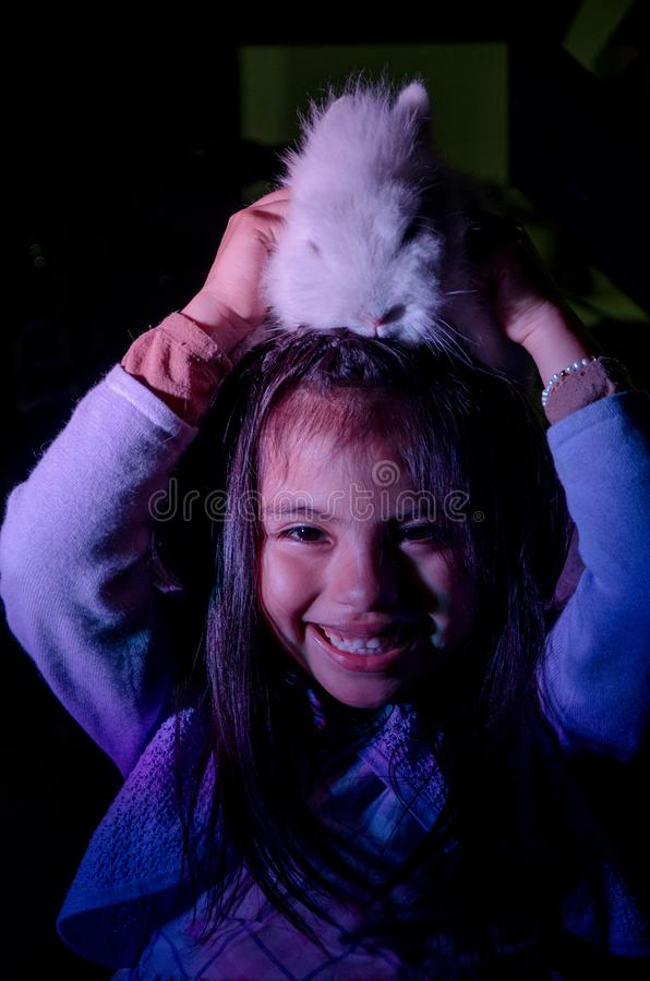 Bambina felice con il suo coniglietto dell'animale domestico sulla sua testa fotografie stock