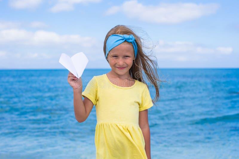 Bambina felice con l'aeroplano di carta in mani sopra fotografia stock libera da diritti